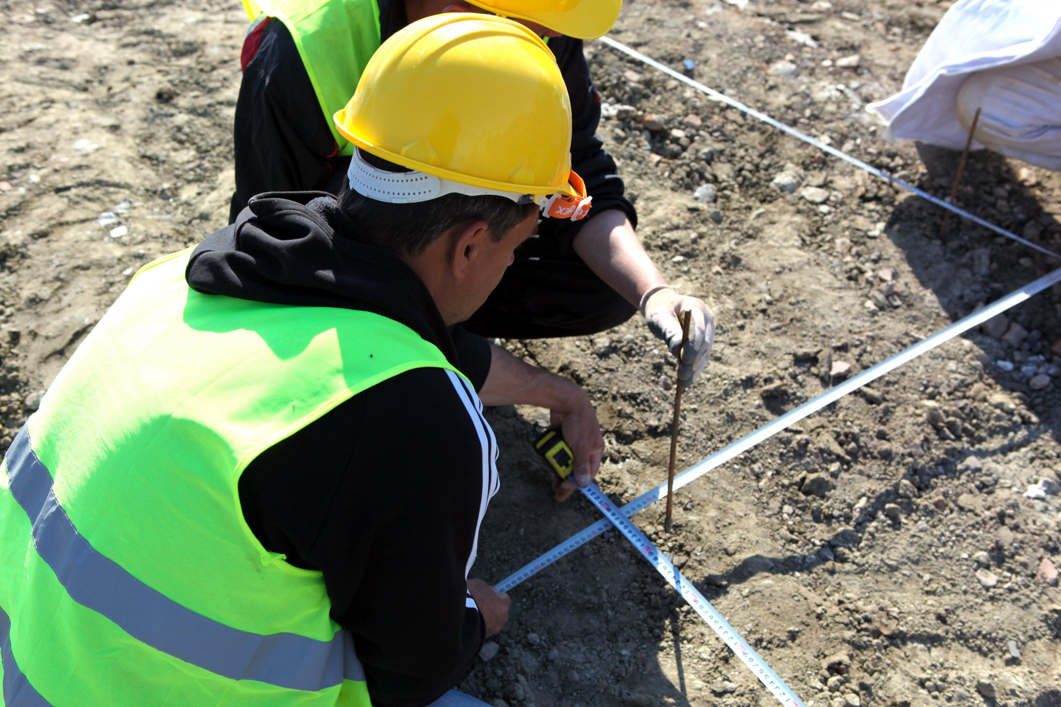 Two Workers Outside Measuring Area for Concrete